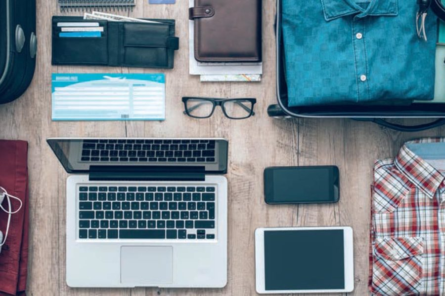 Laptop avec portable tablette, chemises, valises, papiers et billet avion